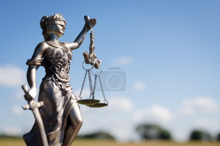 sculpture of themis, femida or justice goddess on bright blue sky copy space background