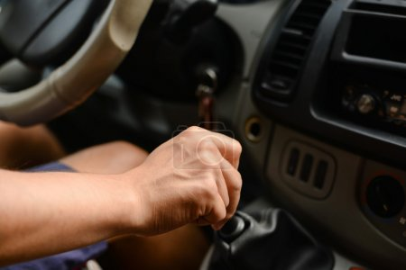 drivers right hand shifting the gear stick in car, close up image