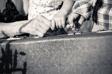 Photo pour Photo en noir et blanc de mères et de deux enfants mains tenant une poignée de valise rétro - image libre de droit