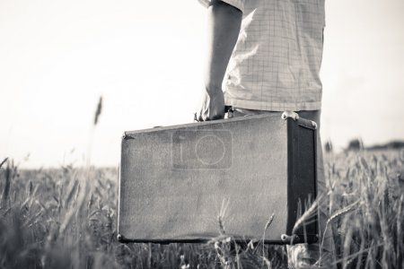 Black and white picture of mans hand   holding retro suitcase