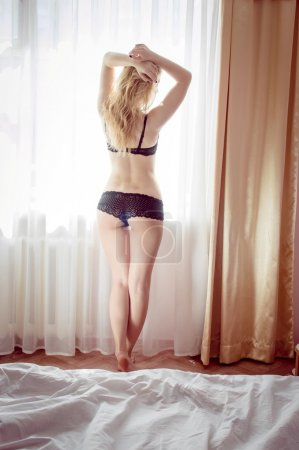 Image of slim glamor girl undressing and showing her perfect fitness shaped body on light window background copy space
