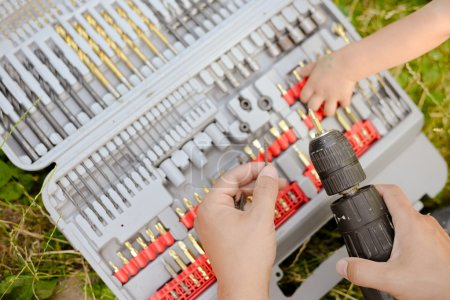 Young and adult hands holding drill, bits and screw. Closeup picture of do it yourself concept.