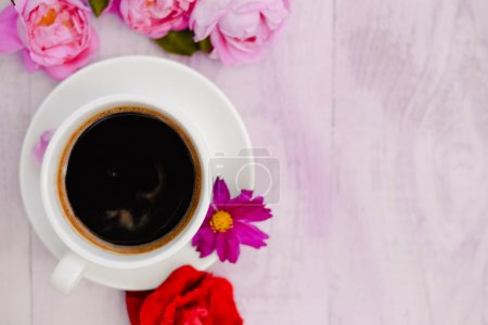 White cup of black coffee and rose petals beside instead of cake  copyspace