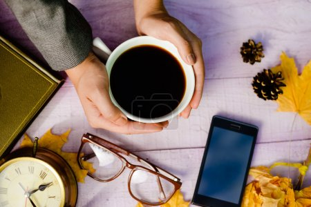Photo for Top view close up on hands holding cup of coffee with mobile phone, glasses and alarm clock over copy space wooden table background - Royalty Free Image