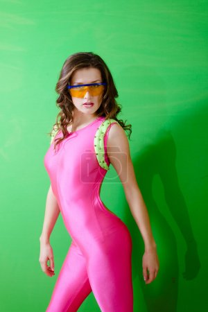 Portrait of sexy young lady wearing pink lycra jum...