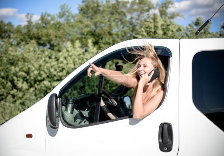 Blond girl driving car speaking on mobile phone and looking out of window