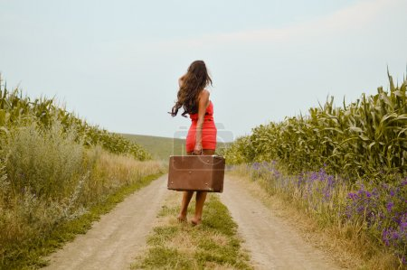 Image of beautiful young woman holding suitcase in hand and walking on sunny day outdoors landscape