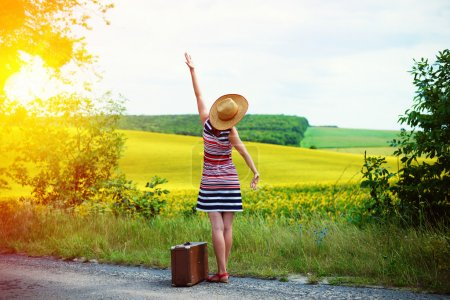 Photo for Picture of young woman in straw hat with retro suitcase beside beautiful summer meadow. Backview of girl standing on sun flare country roadside background - Royalty Free Image