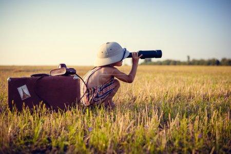 Little boy looking in spyglass on sunny field countryside background.