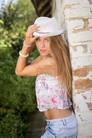 Young girl in fedora hat leaning at old brick fence