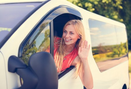 Picture of beautiful blond girl smiling and greeting someone from car window.