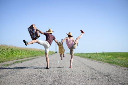 Photo pour Photo de famille joyeuse sautant et dansant sur la route en été. Backview des parents et bébé fille avec valise rétro sur fond de campagne ciel ensoleillé - image libre de droit