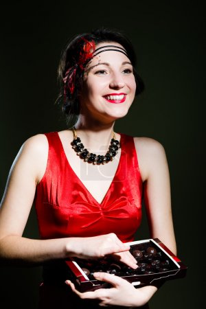 Young beautiful amazing woman in 20s styled red costume with chocolate sweets