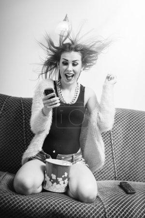 Photo pour Bonne nouvelle : portrait d'une drôle de jeune blonde jolie femme qui s'amuse à regarder un téléfilm avec du pop-corn et qui tient son téléphone portable, heureuse excitée en criant sur fond d'espace de copie légère. Noir et blanc - image libre de droit