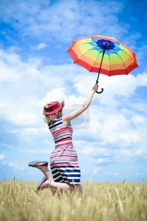 Happy jumping dreaming woman with umbrella in the wheat field