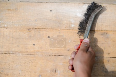 Closeup of scrubbing and cleaning with metal brush on wood