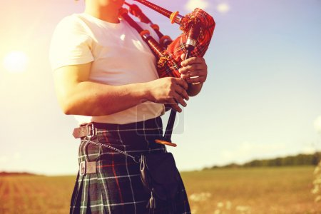 young man playing pipes in national uniform on green summer outdoors copy space background, closeup picture