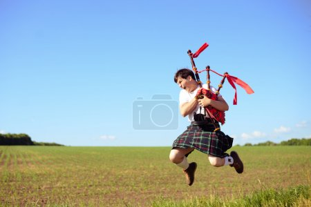 Photo for Portrait of man jumping high with pipes in Scottish traditional kilt on green outdoors copy space summer field - Royalty Free Image