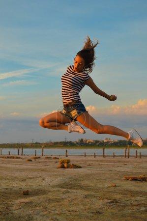 Photo pour Illustration de la jeune dame étonnée belle ayant l'amusement sautant haut au-dessus du fond extérieur d'espace de copie - image libre de droit
