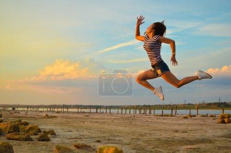 Photo pour Illustration de la belle jeune dame ayant l'amusement sautant haut au-dessus du fond extérieur d'espace de copie - image libre de droit