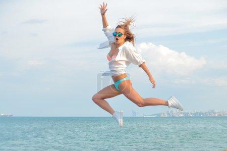Photo pour Illustration de la jeune femme belle étonnée ayant l'amusement dans le saut en hauteur au-dessus du fond extérieur d'espace de copie - image libre de droit