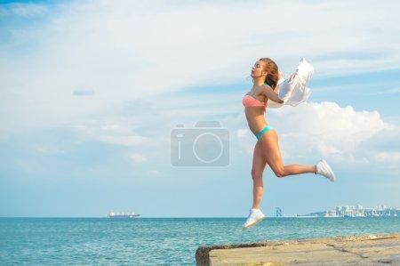Photo pour Illustration de la belle jeune femme ayant l'amusement dans le saut en hauteur au-dessus du fond extérieur d'espace de copie - image libre de droit