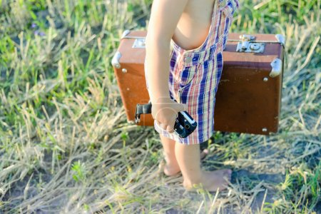 Little boy with old suitcase and shock-proof mobile phone walking