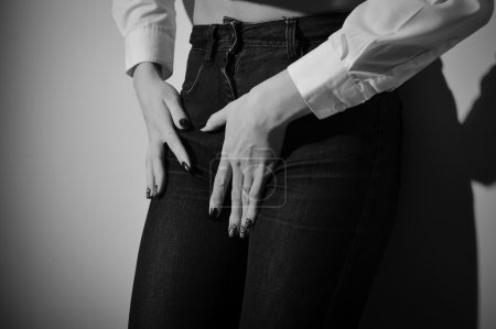 Seductive female wearing jeans long sleeve short and trousers on light background. Black and white photography