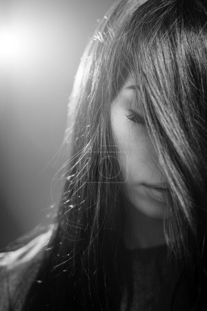 Photo for Closeup black and white photography of dreaming beautiful girl holding eyes closed posing on light flare copy space background - Royalty Free Image