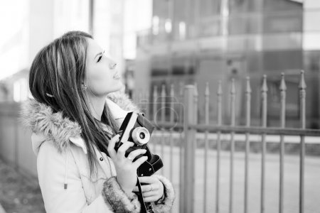 Photo pour Photographie noir blanc de belle jeune femme tenant un appareil photo sur fond de bâtiment en verre de la ville - image libre de droit