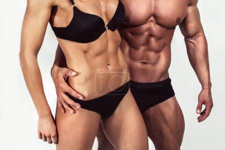 Photo pour Carrosserie. Homme fort et une femme posant sur fond blanc en studio - image libre de droit