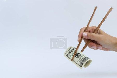 Rouleau de 100 dollars en baguette de bois sur un blanc avec une place pour ext.