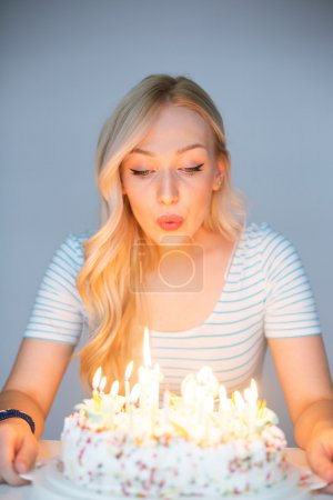 bautiful caucasian girl blowing candles on her cake