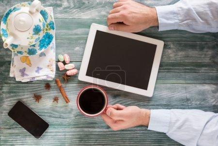 hand using mockup tablet similar to ipad style on wood desk whit