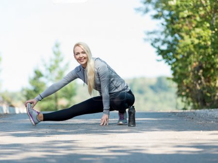 Fitness woman doing streching during outdoor cross training work