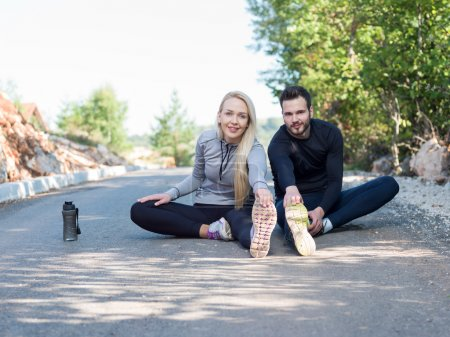 young health couple doing stretching exercise relaxing and warm