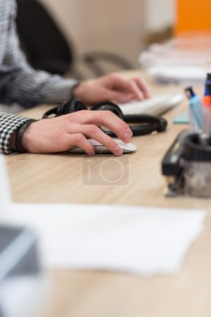 Man's hands working with computer mouse and computer keyboard