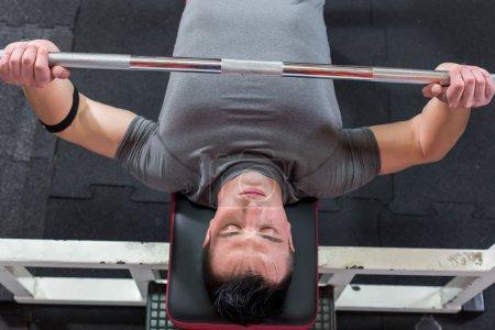 Photo pour Jeune homme dans la salle de gym exercice poitrine sur la presse banc - vue du haut - image libre de droit