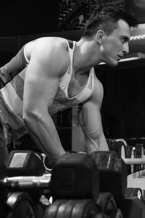 Fitness athletic sportsman doing workout with dumbbells in a gym