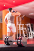 Big dumbbells with active body builder in background
