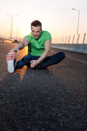 Stretching after jogging. sunset shot on highway