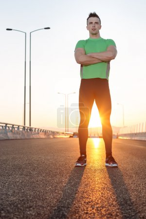 Portrait of male runner taking break after run while standing on