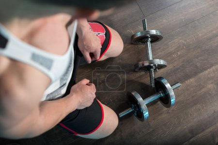 Top view of man in a gym on wooden background with weights