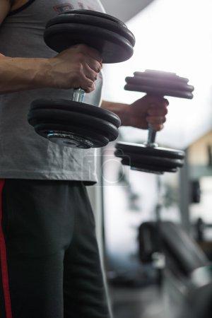 Closeup of a muscular young man lifting weights, Caucasian man