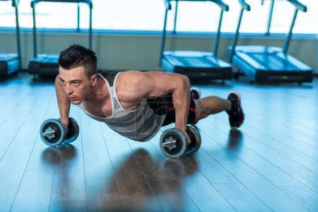 Muscular man doing push-ups on dumbbells in gym. Powerful male e