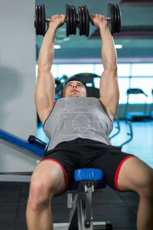 Muscular Young Man Doing Heavy Weight Exercise For Biceps With D