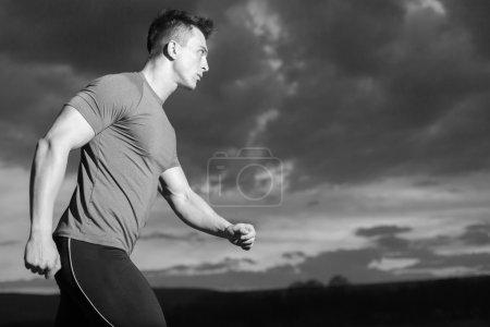 Photo pour Jeune homme souriant en vêtements de sport posant dans la rue souriant, coureur se reposant dans la nuit de la rue. mode de vie actif - image libre de droit