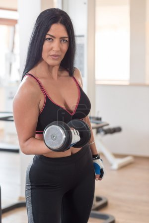 Woman weight lifting with exercise equipment in health club, por