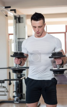 Muscular bodybuilder guy doing exercises with dumbbells in gym