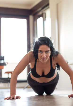 Portrait of a fit and muscular woman doing intense core workout